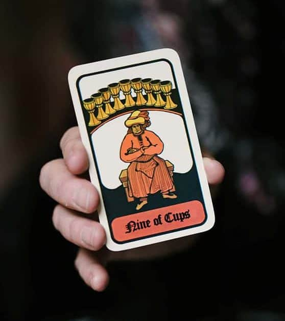 A hand holding a Nine of Cups Tarot card.