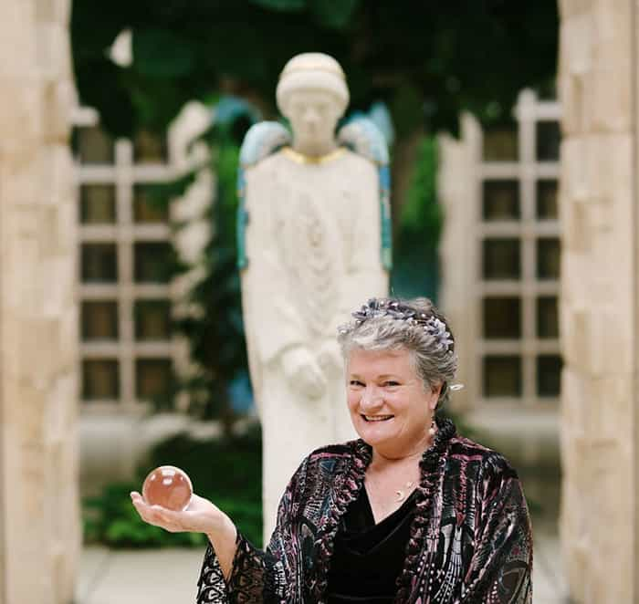 Mary Kay seated in front of angel statue holding crystal ball in the palm of her right hand.